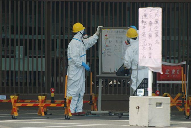 Guards at whiteboard at Fukushima-1 main gate
